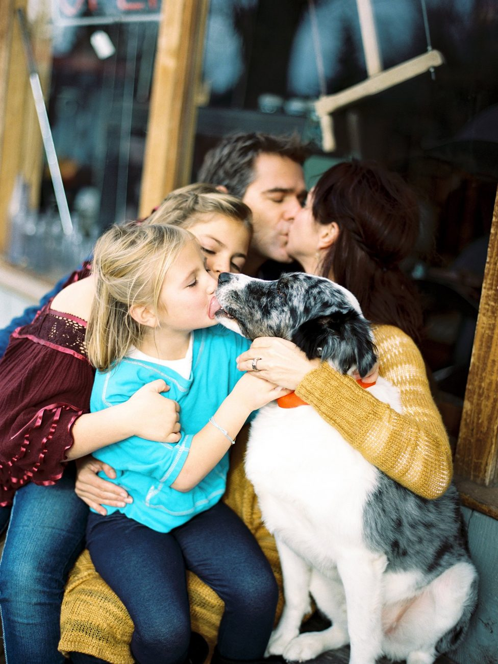 Family kissing their dog.