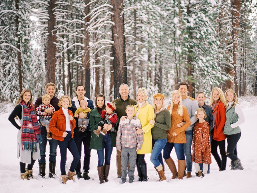 Big family portrait in winter with snow covered trees. Family photography by Marina Koslow.