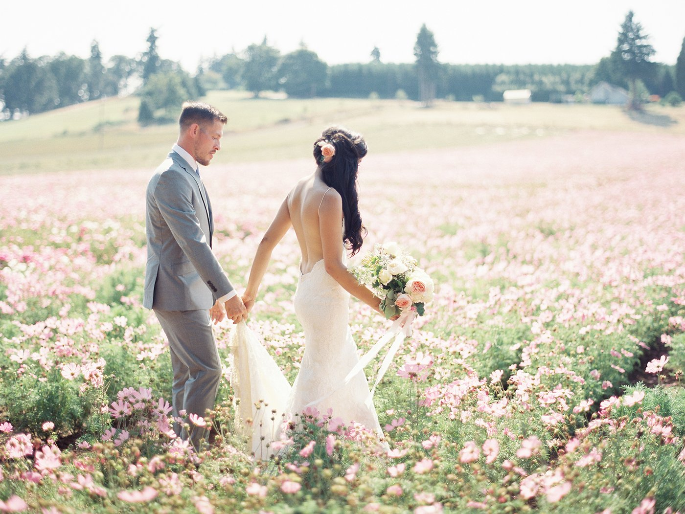 Bride and groom walking through a flower field