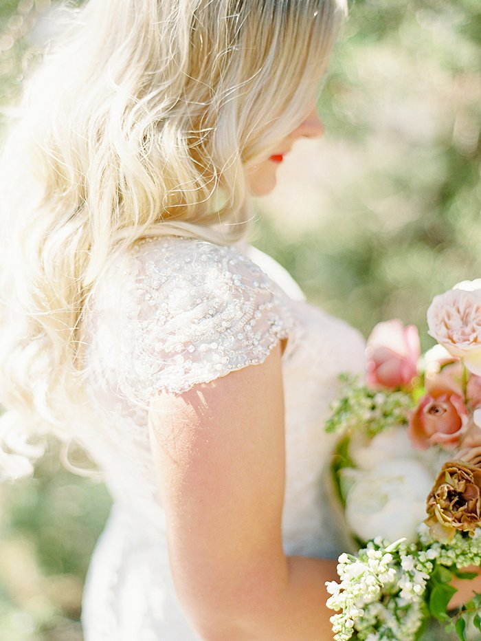 Bride holding flowers at her wedding in Central Oregon, photography by Marina Koslow.