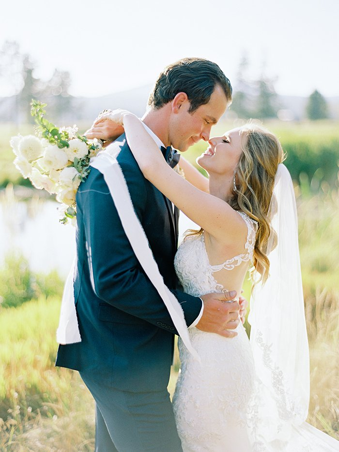 bride and groom kiss at the Great Hall in Sunriver Oregon