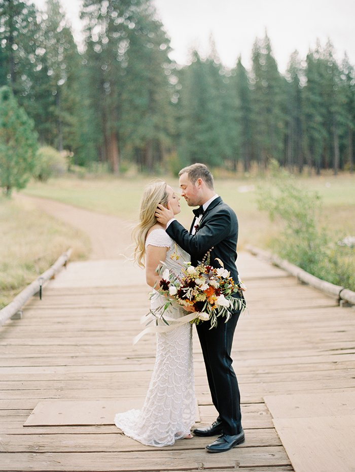 bride and groom kiss on bridge over Metolius River